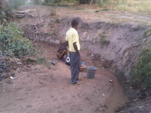 Villagers scavenging water  from a 'stream'